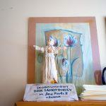 Mała rzeźba przedstawiająca Jana Pawłą II. Za rzeźbą obrazy w ramkach