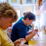 Kobiety siedzą przy stole i ucinają nitki nozyczkami