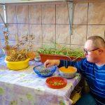 Mężczyzna w swetrze w paski siedzi przy stole i dotyka nasiona, które znajduja się w misce