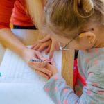 Dziewczynka uczy się pisać pod opieką nauczycielki