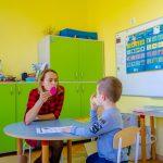 Chłopiec siedzi przy stole podczas zajęć logopedycznych po opieką specjalistki