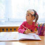 Dziewczynka z opaską na głowie wypełnia zadania w książce