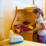 Dziewczynka bawi się dziecięca kuchnią z tyłu różowy wózek