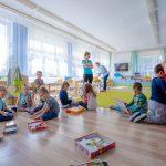 Dzieci siedzą na podłodze i bawią sie puzzlami