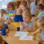 Dzieci siedzą przy stołach i rysują na kartkach