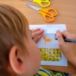 Chłopiec rysuje zwierzątko. Na stole leżą nożyczki