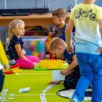 Dzieci bawią się zabawkami na zielonej podłodze