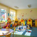 Dzieci bawią się na podłodze kolorowego pomieszczenia. Z tyłu kolorowe szafki