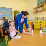 Trójka dzieci siedzi przy stole, nauczycielka w niebieskim swetrze kładzie na stole kartkę. Z tyłu siedzi kobieta przy laptopie