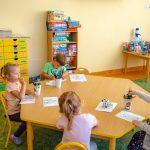 Dzieci siedzą przy stole i rysują