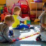 Trzech małych chłopców bawi się na podłodze. Chłopiec klęczy i patrzy sie w obiektyw