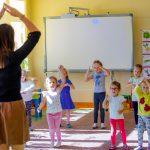 Kobieta podnosi ręce i łączy dłonie nad głową. Przed nia grupa dzieci, która naśladuje jej ruchy