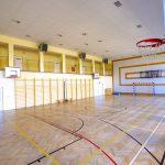 Duża sala gimnastyczna z jasnym parkietem. Na parkiecie wymalowane linie do gier zespołowych. Na