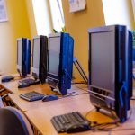 Wygaszone monitory koloru czarnego i klawiatury ustawione na biurkach. Przy biurkach fotele obrotowe