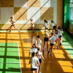 Dziewczyny w strojach gimnastycznych biegną w szeregu po sali gimnastycznej