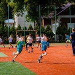 Chłopcy w strojach sportowych biegaja po boisku. Nawierzchnia ma kolor ceglasty i zielony