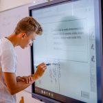 Chłopiec w białym t-shircie pisze na tablicy interaktywnej