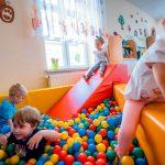 Dzieci bawią się w basenie z kolorowymi piłeczkami