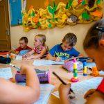 Dzieci w kolorowych bluzkach siedzą przy stole i piszą