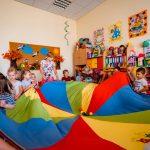 Dzieci bawią się kolorowym dywanem