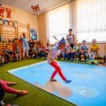 Dziewczynka w czerwonych rajstopach chodzi po podłodze interaktywnej , wokół dzieci