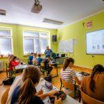 Uczniowie siedzą w ławkach w sali pomalowanej na kolor zielony. Na ścianie wiszą monitory interaktywne