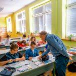 Nauczyciel pochyla się nad ławką, przy której siedzą uczniowie i coś objaśnia