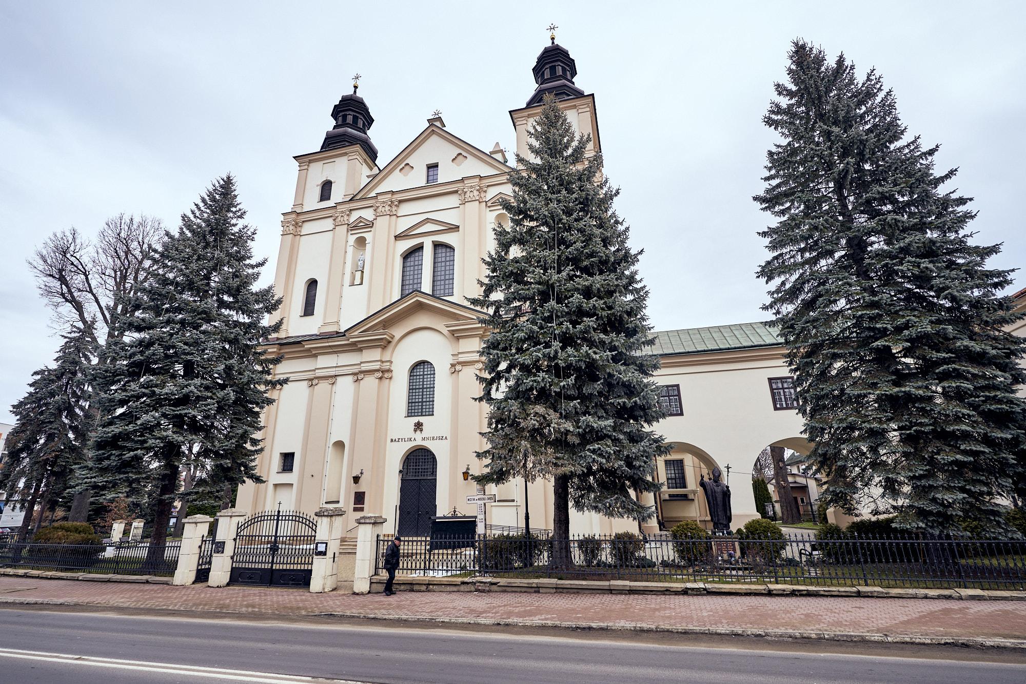 Zabytkowy kościół z dwoma wieżami. Elewacja koloru beżowego. Przed kościołem rosną drzewa