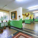 Korytarz w szkole z kolorowymi ścianami i podłogą. Na ścianach obrazy i malunki