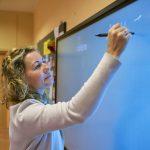 Kobieta z kręconymi bląd włosami pisze na cyfrowej tablicy