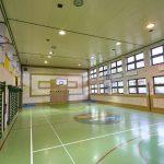 Sala sportowa z boiskiem do piłki ręcznaj. Na jednej ze ścian drabinki i kosz