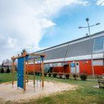 Bydynek hali sportowej z czerwoną elewacją. Przed halą plac zabaw