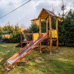 Kolorowa zjeżdżalnia na placu zabaw usytuowanym na zielonym trawniku
