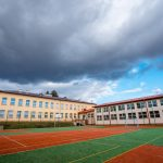 Dwukondygnacyjne budynki szkolne ze spadzistymi dachami. Przed budynkami boisko sportowe ze sztuczną nawierzchnią
