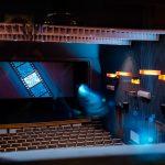 Kolorowo iluminowana sala kinowa z rzędami jasnych krzeseł
