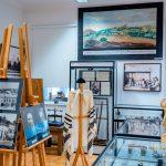 Eksponaty muzealne w gablotach oraz stare zdjęcia ustawione na sztalugach