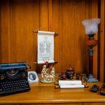 Czarna maszyna do pisania, lampa naftowa i inne eksponaty ustawione na drewnianej półce