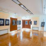 Sala wystawowa z kolekcją czarno-białych zdjęć w antyramach