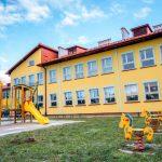 Dwukondygnacyjny budynek szkoły w kolorze żółtym pokryty czeerwonym spadzistym dachem. Przed budynkiem plac zabaw