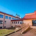 Trókondygnacyjny budynek szkolny z podjazdem dla osób niepełnosprawnych. W głebi barokowy kościół z dwoma wieżami