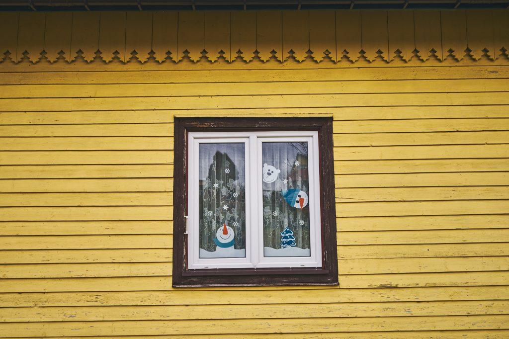 Okno w drewnianym budynku w kolorze żótym