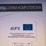 Białe drzwi, nad nimi czarna tablica z białym napisem. Na drzwiach tablica z flagą europejską i napisem EFS