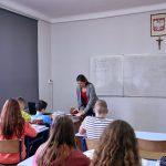 Klasa szkolna, uczniowie siedzą w ławkach. Nauczycielka pochyla się nad stołem. Na ścianie godło Polski i krzyż
