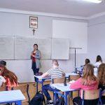 Klasa szkolna, uczniowie siedzą w ławkach. Nauczycielka stoi przy tablicy. Na ścianie godło Polski i krzyż