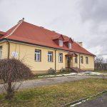 Budynek szkolny z czerwonym dachem. Ściany elewacji pomalowane na żółto.