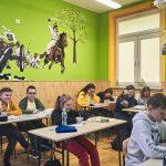 Dzieci siedzą w ławkach w klasie. Na ścianie koloru zielonego namalowana scena bitewna
