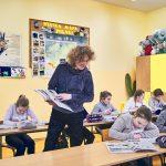 Nauczycielka z książką w ręce patrzy na dzieci siedzące w ławkach i odrabiające zadanie