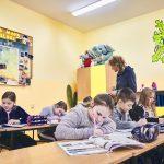 Dzieci siedzą w ławkach i pisza w zeszytach. Z tyłu na ścianie wisi mapa Polski