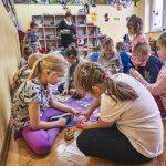 Grupa dzieci siedzi i klęczy na dywanie podczas zabawy