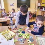 Dwóch chłopców w kolorowych swetrach gra w puzzle rozłożone na stole. Z tyłu dwie dziewczynki siedzą przy stole